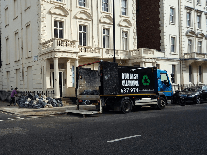 Blue Skip man & lorry at work in Central London